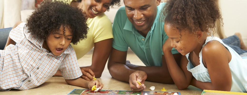 An African-American family playing a board game at home.