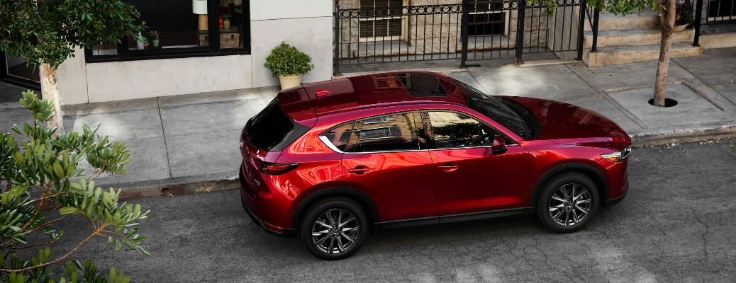 The top and side view of a red 2021 Mazda CX-5 parked on the side of a street.