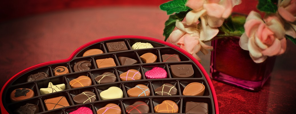 A box of Valentine's Day chocolates next to a set of flowers.