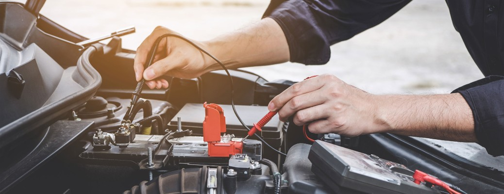 A man testing the battery inside a Mazda vehicle.