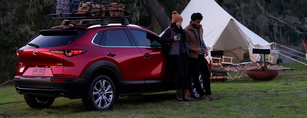 A young couple leaning against a red 2021 Mazda CX-30 in an open space.