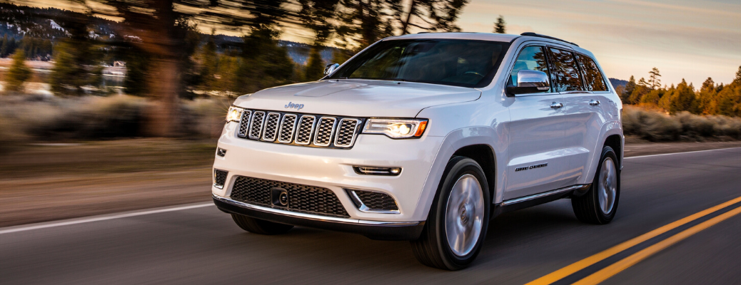 Front view of white 2020 Jeep Grand Cherokee Summit on the road
