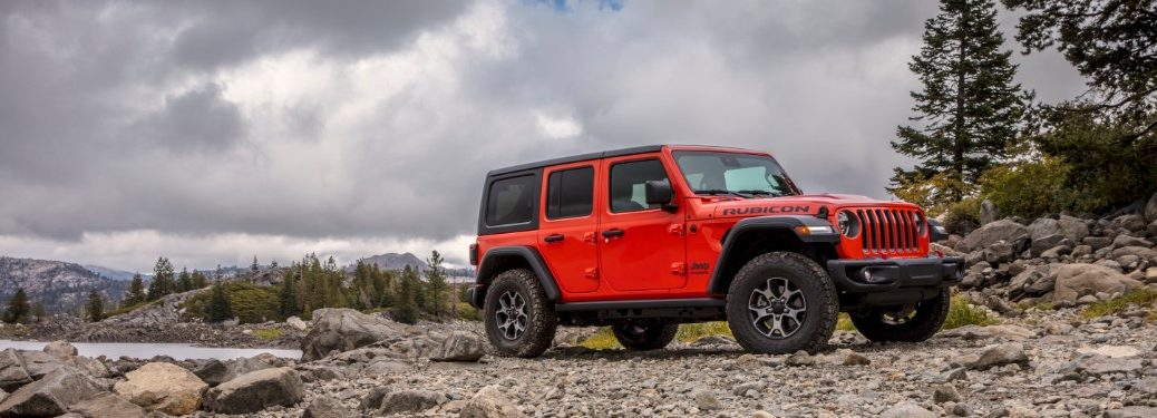 2021 Jeep Wrangler parked in forest near lake