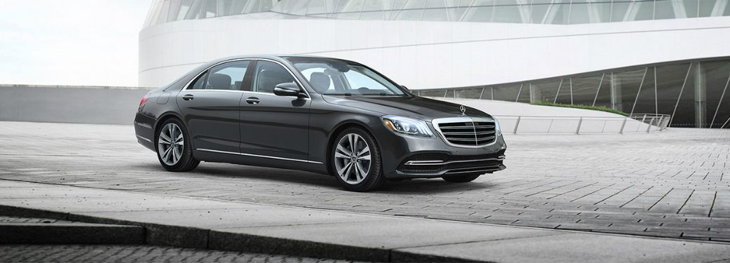gray mercedes-benz s-class parked on a brick road near a building