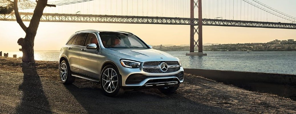 2020 Mercedes-Benz GLC SUV parked by side of river with suspension bridge in background at sunset