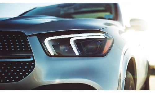 2020 Mercedes-Benz GLE exterior shot close up of headlight with part of bumper and bright light in background