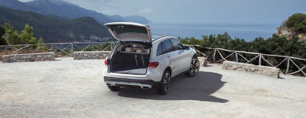 2020 Mercedes-Benz GLC SUV parked on cliff overlooking mountains and water facing away showing open trunk shadows