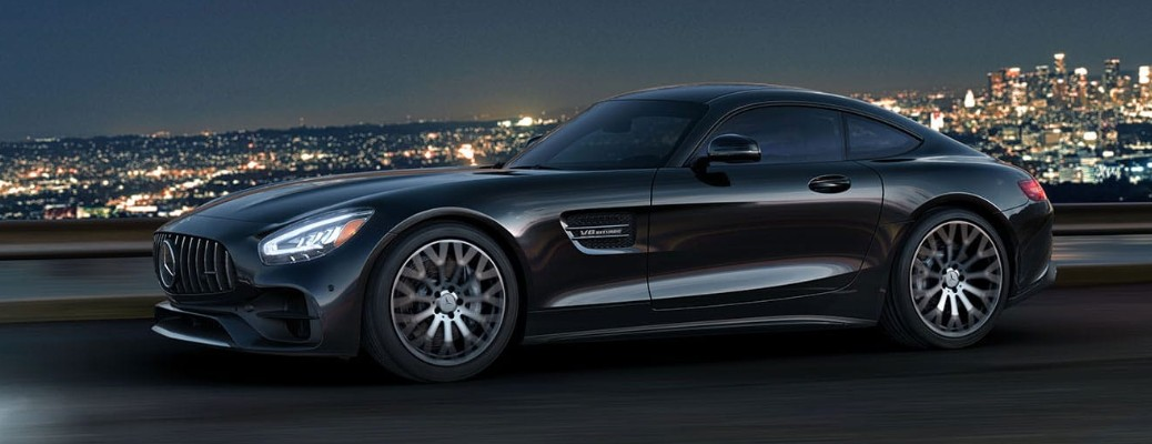 Side view of black 2020 Mercedes-AMG® GT Coupe with a city skyline in the background