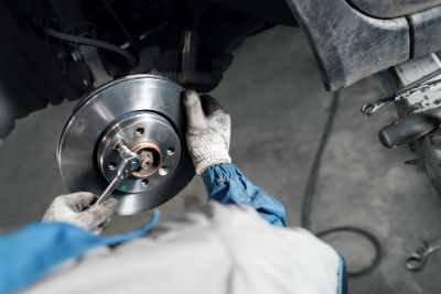 mechanic replacing vehicle brakes
