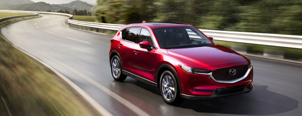 Red 2021 Mazda CX-5 driving on wet road