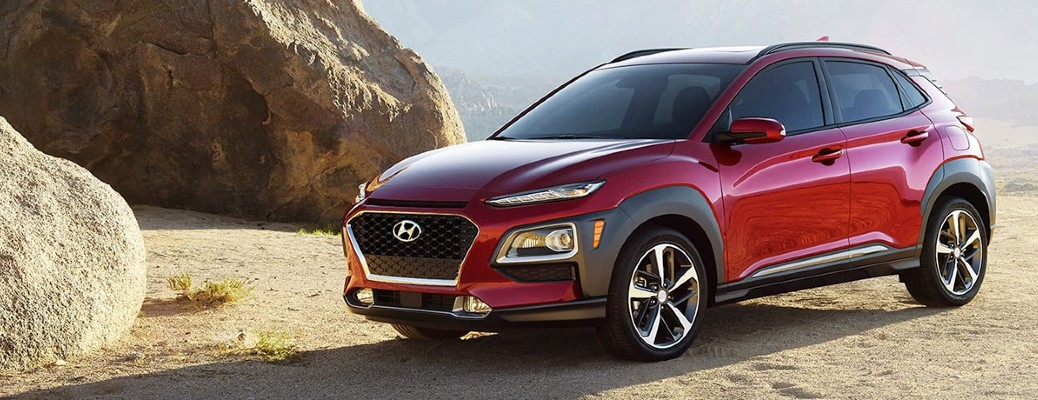 2020 Hyundai Kona red exterior driver side front parked in desert with large rocks