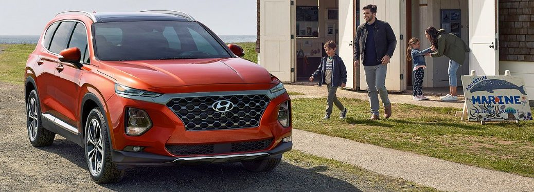 2020 Hyundai Santa Fe orange exterior front passenger side parked in front of building family walking out
