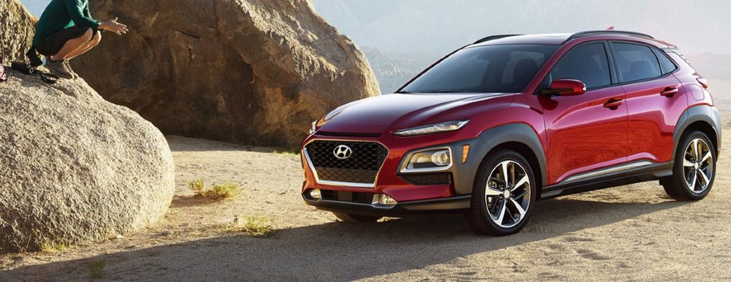 2021 Hyundai Kona red exterior front fascia driver side parked in desert man crouching on rock