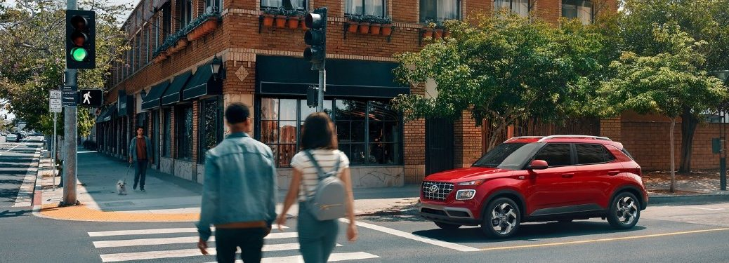 red 2021 Hyundai Venue drive side front fascia stopped at intersection couple in crosswalk