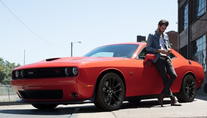 A man leaning on a 2020 Dodge Challenger