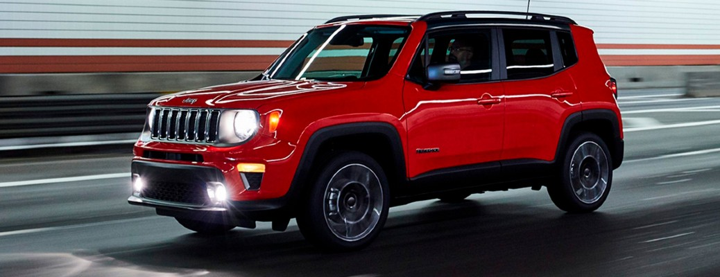 A red-colored 2021 Jeep Renegade driving on a road
