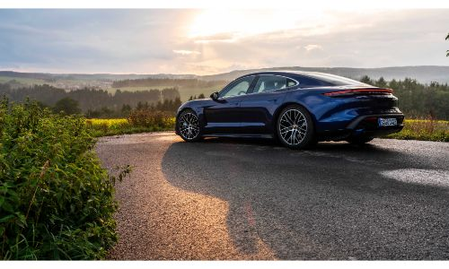 2020 Porche Taycan blue parked overlooking trees