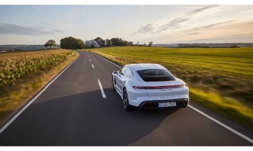 2020 Porsche Taycan white viewed from behind driving on road between fields