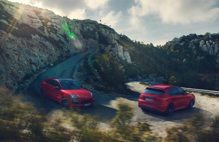 two red Porsche Cayenne driving down hill