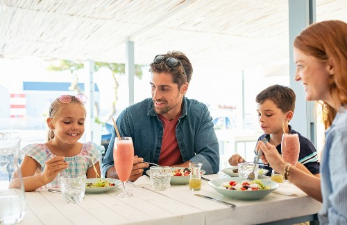 family of four enjoying a meal at a restaurant outdoors