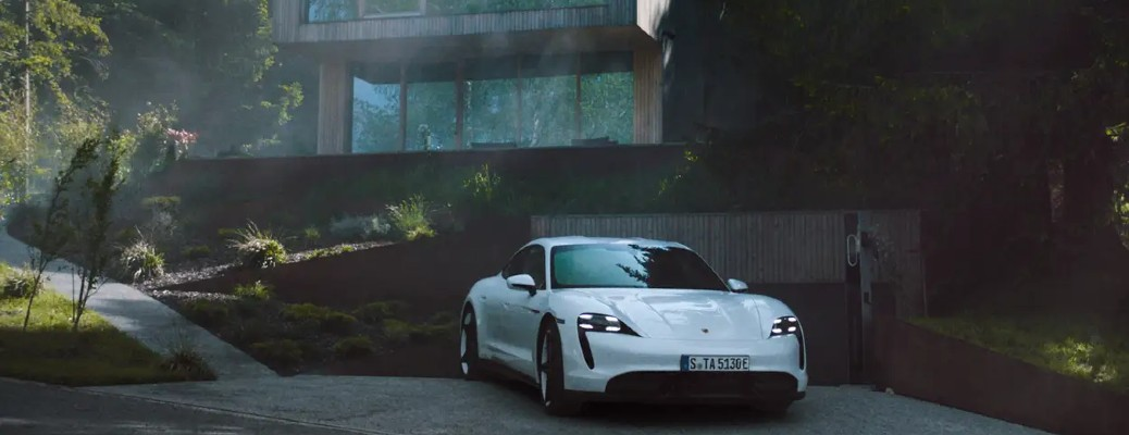 Porsche Taycan Cross Turismo white exterior front fascia parked in front of house