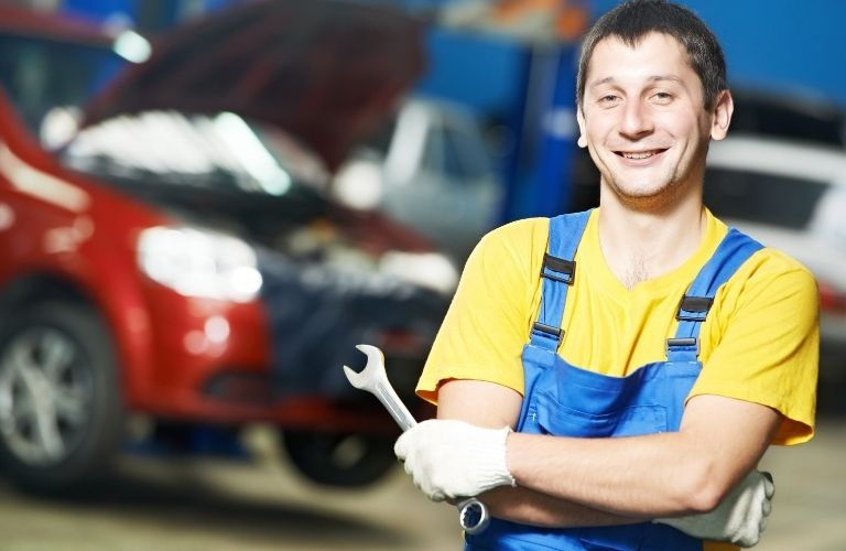 A mechanic posing with a wrench on his hand