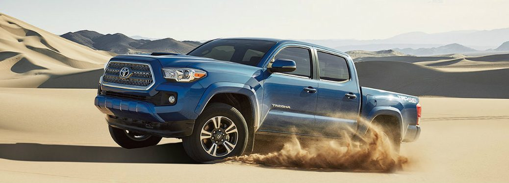 Exterior View of the 2017 Toyota Tacoma in Blue Driving on Sand