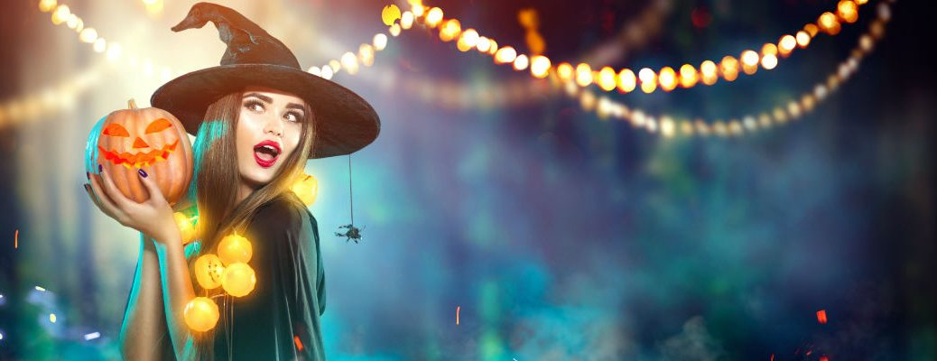 Witch Holding Pumpkin Under Strings of Lights