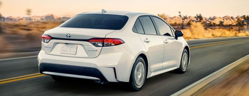 White 2020 Toyota Corolla Hybrid driving down road