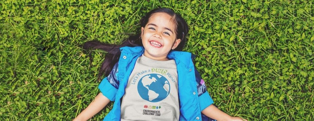 """Young girl laying in grass wearing """"Let's Make a Better Planet"""" Environmental Challenge 2050 shirt"""