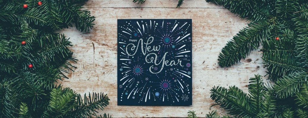 """Happy New Year"" chalkboard sign surrounded by pine tree needles"