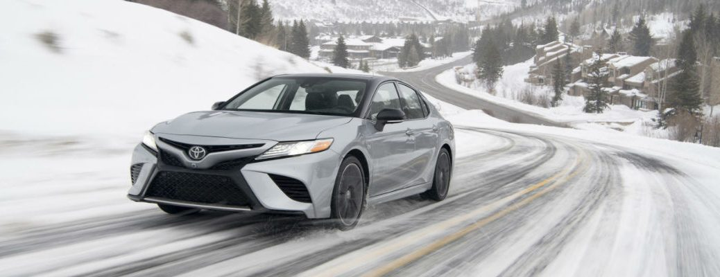 A head-on photo of the 2020 Toyota Camry with AWD on a snowy road.
