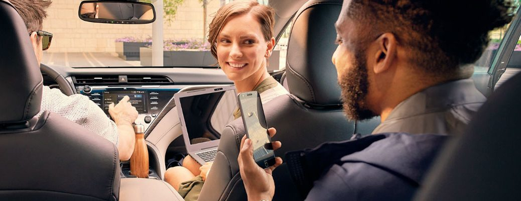 A stock photo of people using the available technology in a Toyota vehicle.