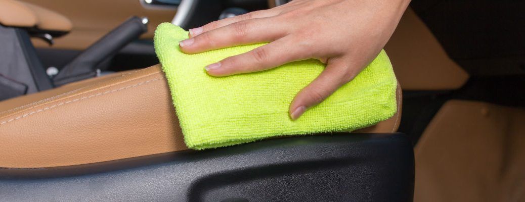 A stock photo of a person cleaning the inside of their vehicle.