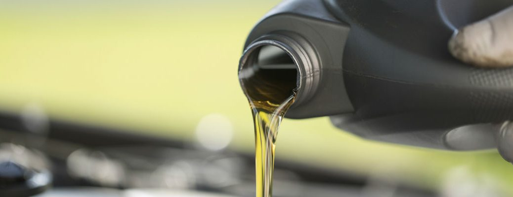 A stock photo of a oil being poured into a vehicle's engine.