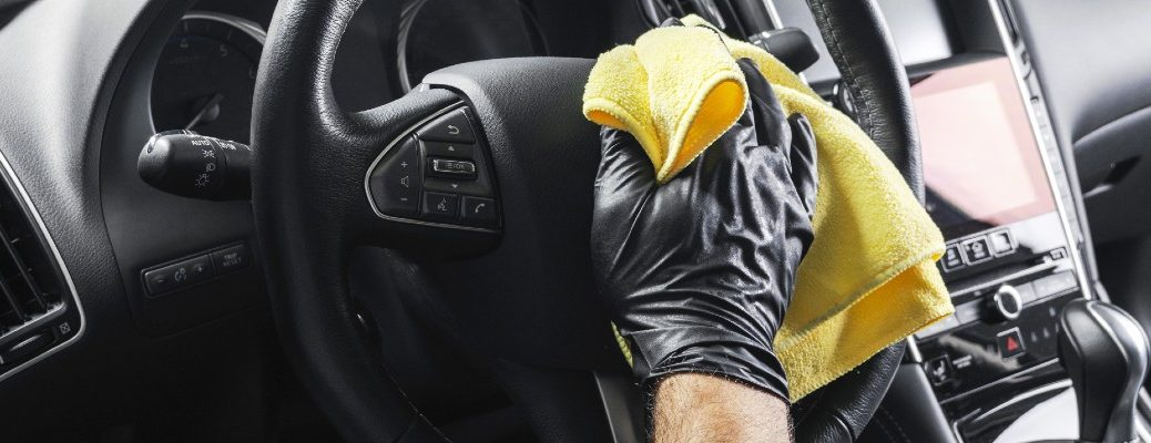 A stock photo of a person wiping down the inside of a vehicle.