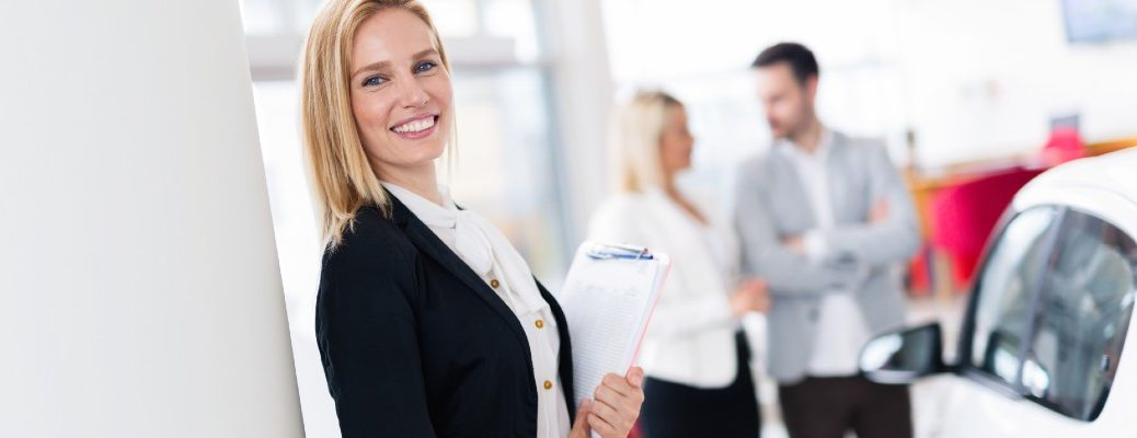 A stock photo of a person helping people at the dealership.