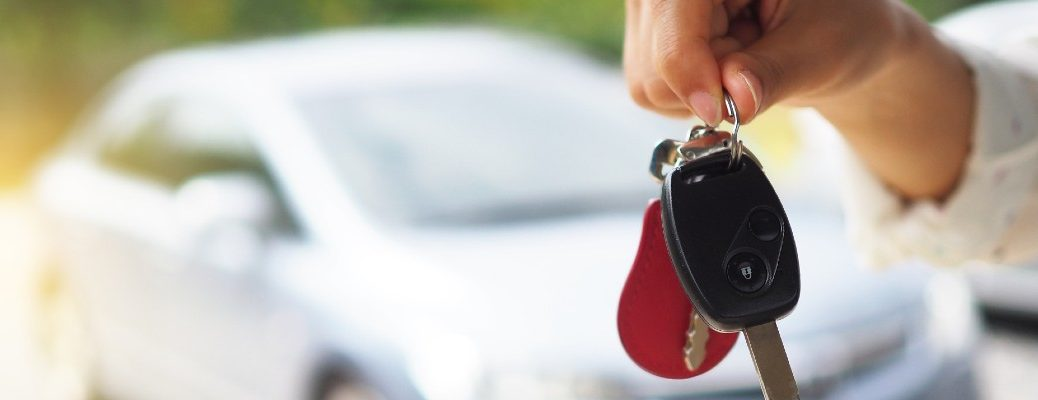 A stock photo of a person holding keys in front of a vehicle they purchased.