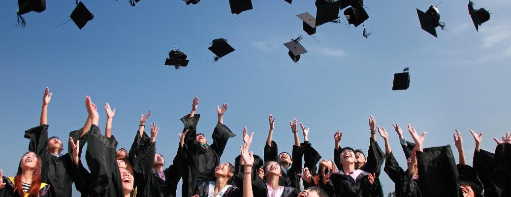 A stock photo of recent graduates tossing their mortarboards in the air.