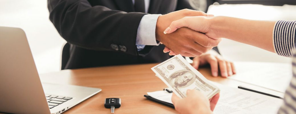 A stock photo of two people exchanging money after completing a transaction