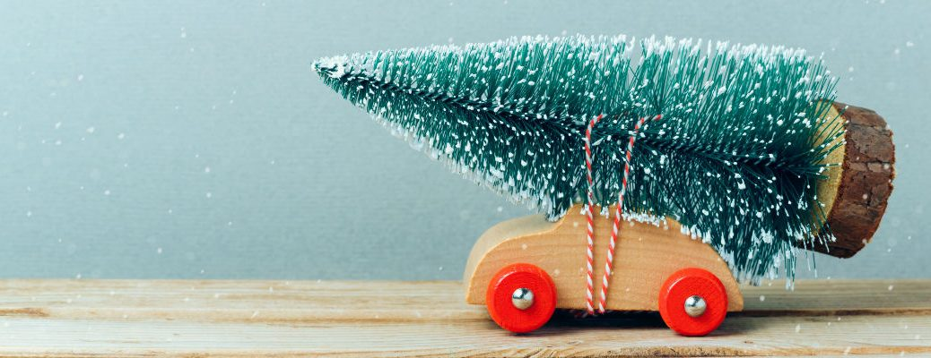A stock photo of wooden toy car with a Christmas tree tied to it