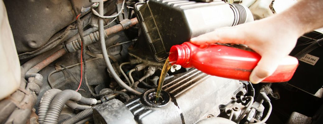 A stock photo of a hand pouring fresh motor oil into an engine