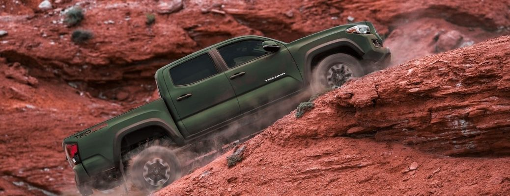 2021 Toyota Tacoma driving on rocks side view
