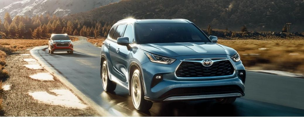 A 2021 Toyota Highlander driving on the road with a car behind it.