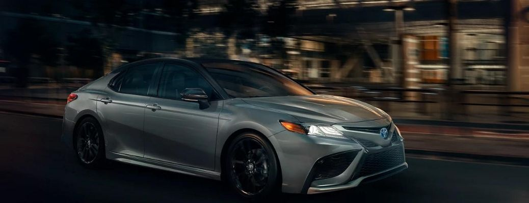 The 2022 Toyota Camry cruising on city road at night.