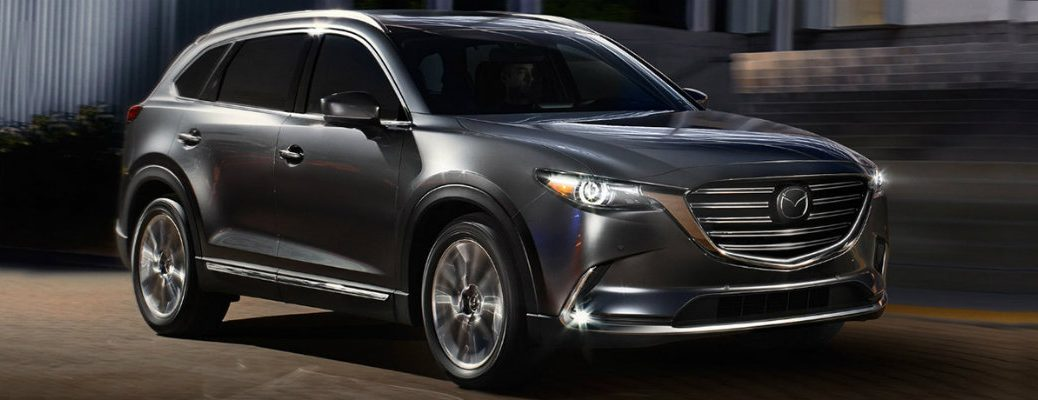 Long shot of silver Mazda CX-9 driving at night in front of brick building