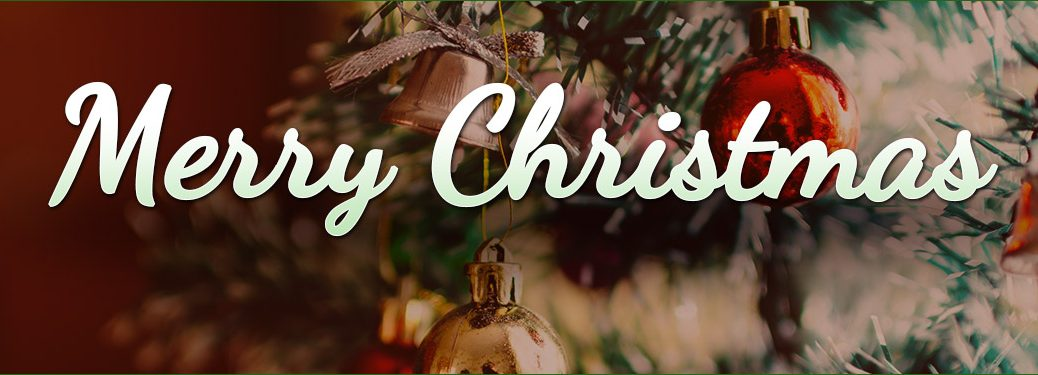 """Christmas tree with ornaments and tinsel with """"Merry Christmas"""" written at forefront of image"""