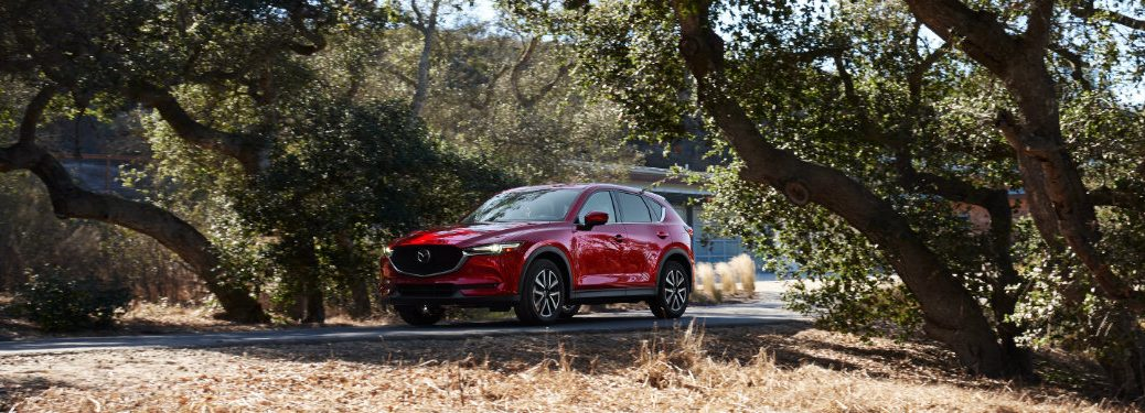 Long view of red 2018 Mazda CX-5 driving on tree-lined street