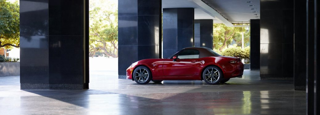 red mazda mx-5 miata parked in marble and concrete structure