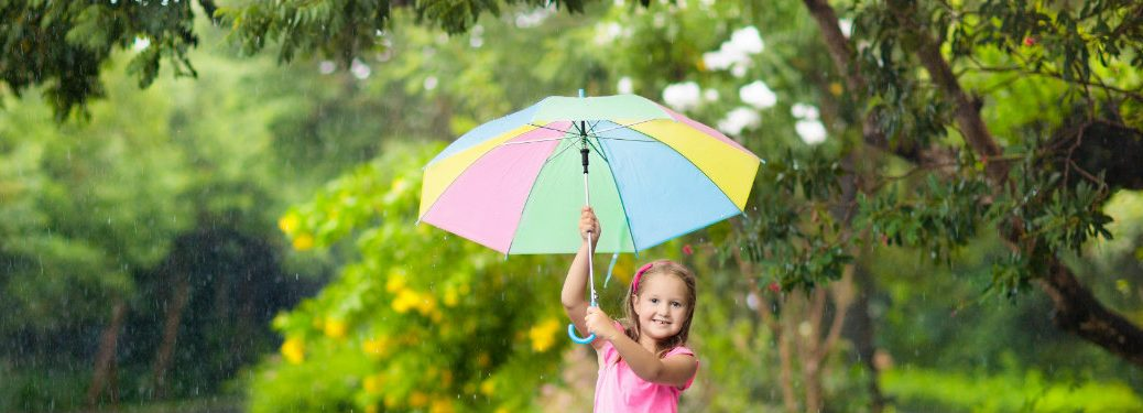 young girl smiling and holding umbrella